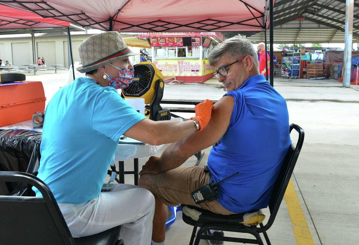 Travis Drescher (right) gets his shot from Nurse Practioner Olga Tsvetkova during a Metro Health pop up COVID vaccine clinic at Traders Village Sunday.
