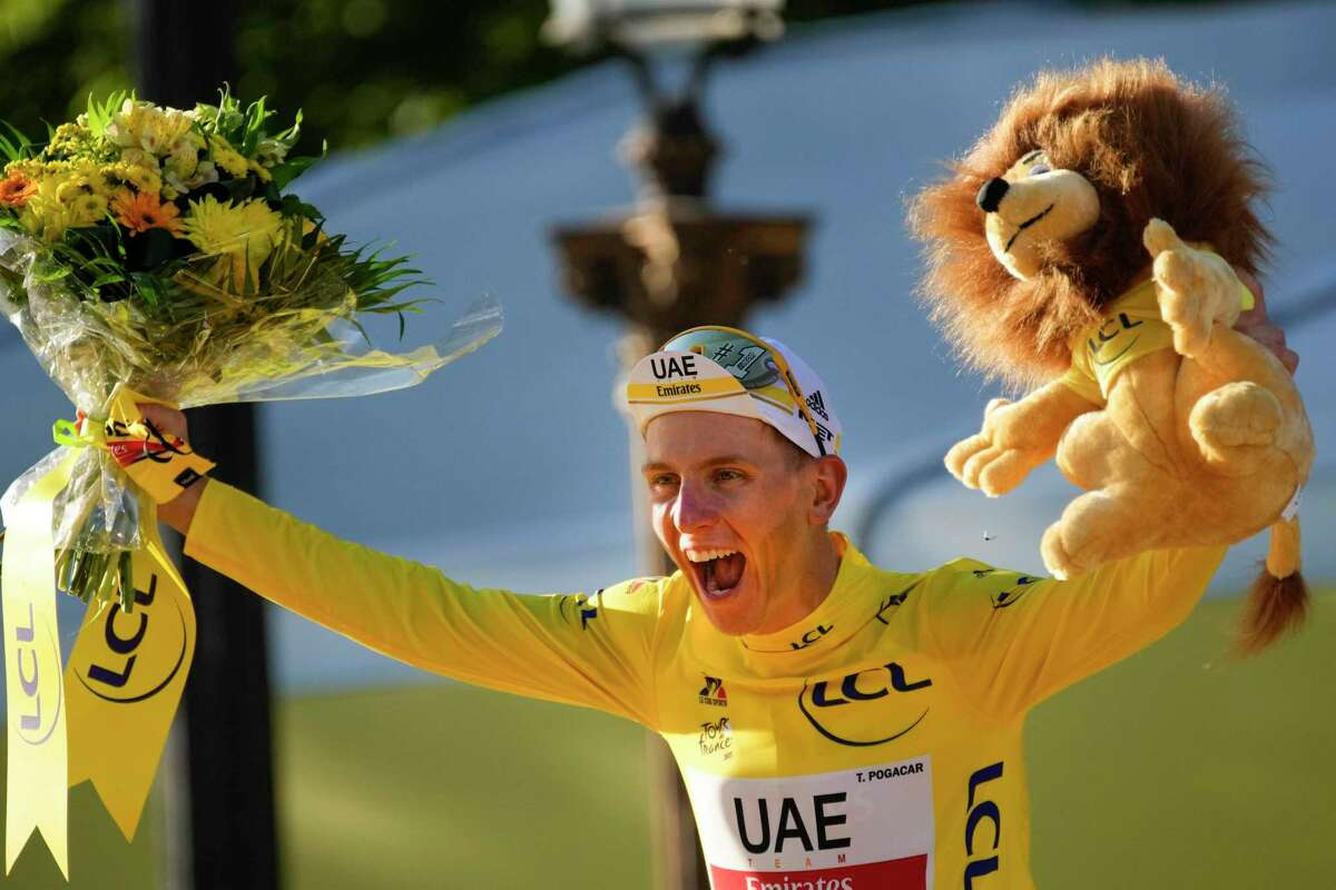 Slovenian cyclist Tadej Pogacar celebrates on the podium in Paris after the 21st and final stage of the Tour de France.