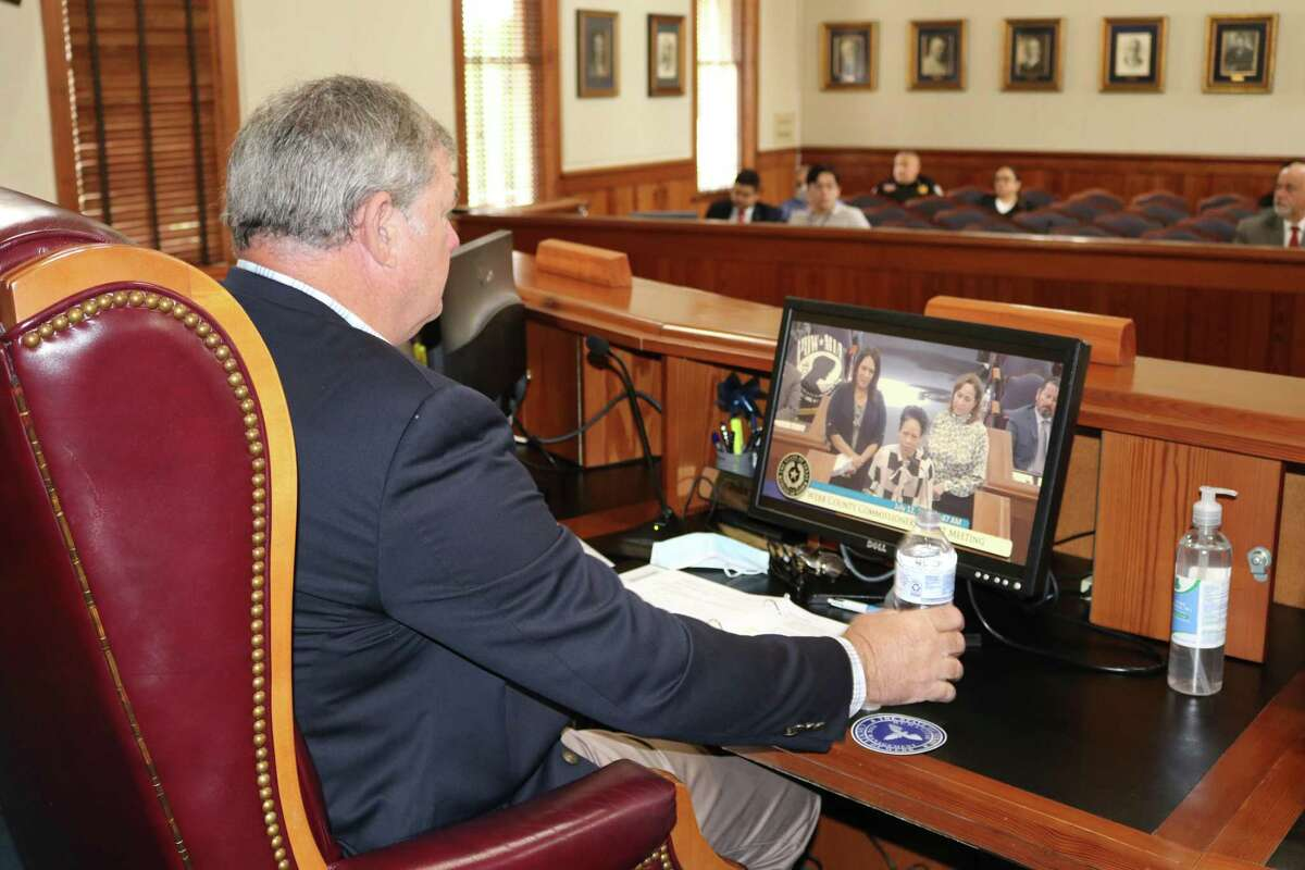 Commissioner John Galo views a TAMIU presentation at commissioners court.