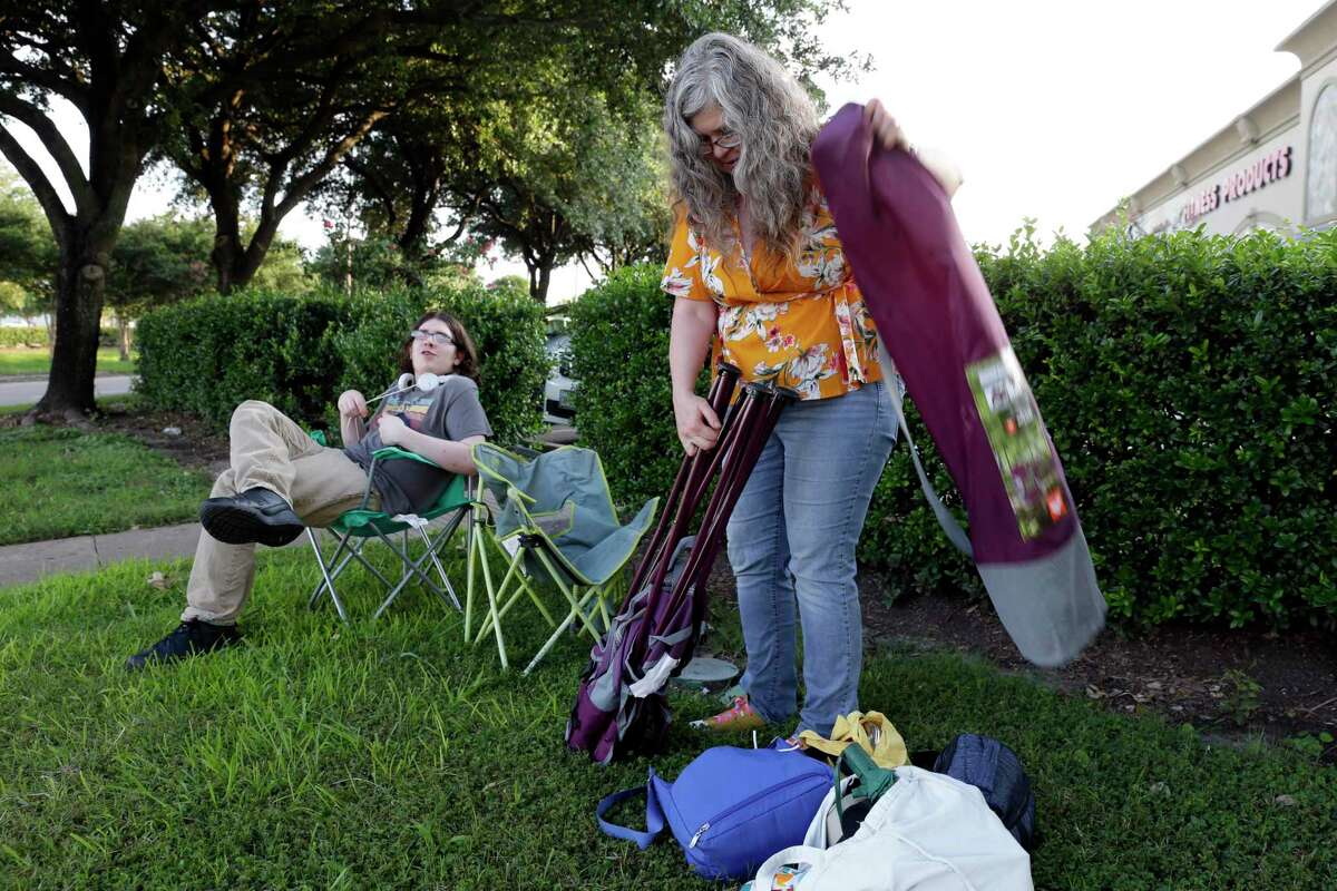 Jaseer Womack, left, and his mother Laura Barnard, right, set up chairs as they prepare to watch the purple martin migration into the trees of a shopping center near the Willowbrook Mall as they prepare to land for the night during their annual southern migration Sunday, Jul. 18, 2021 in Tomball, TX.