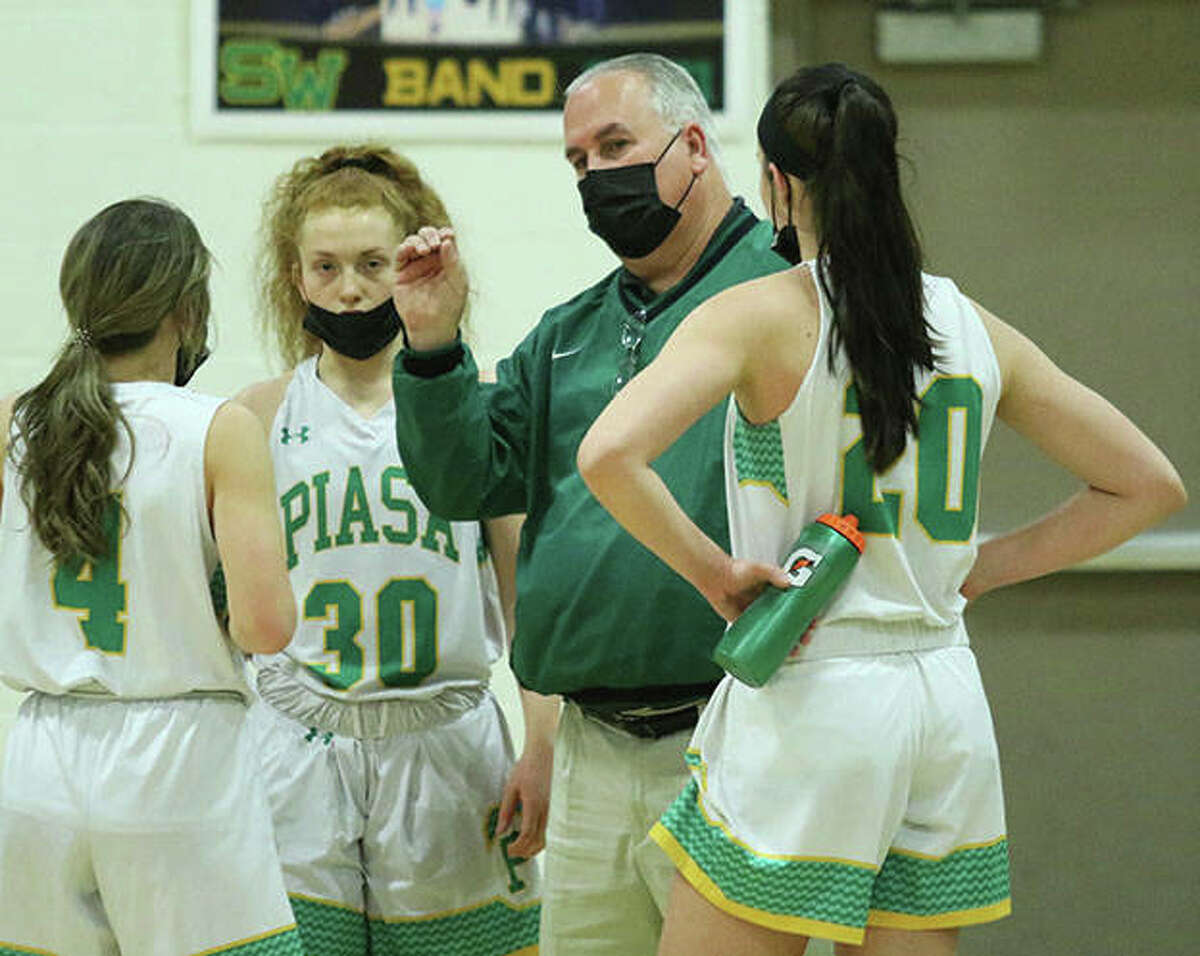 Southwestern coach Steve Wooley talks with seniors Josie Bouillon (4), Rylee Smith (30) and Korrie Hopkins (20) during a timeout in a game last season in Piasa. Wooley, retired after his 24th season with the Piasa Birds, is the 2021 Telegraph Small-Schools Girls Basketball Coach of the Year.