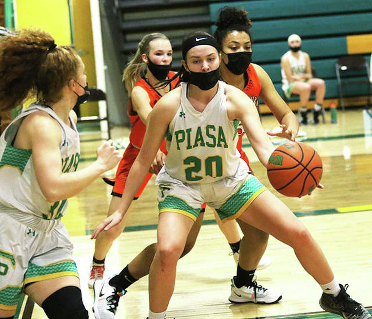 Southwestern senior Korrie Hopkins (20) taps a pass back to Southwestern senior Rylee Smith (left) after she inbounded the ball during a March 6 game against Hillsboro in Piasa. Smith and Hopkins are the 2021 Telegraph Small-Schools Girls Basketball Co-Players of the Year.
