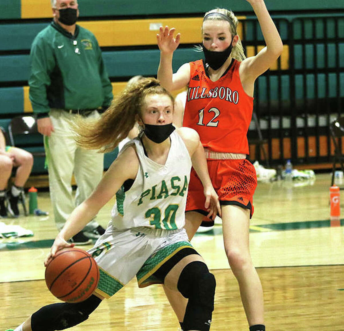 Southwestern's Rylee Smith (30) drives past Hillsboro's Layne Rupert during in a SCC game last season in Piasa.