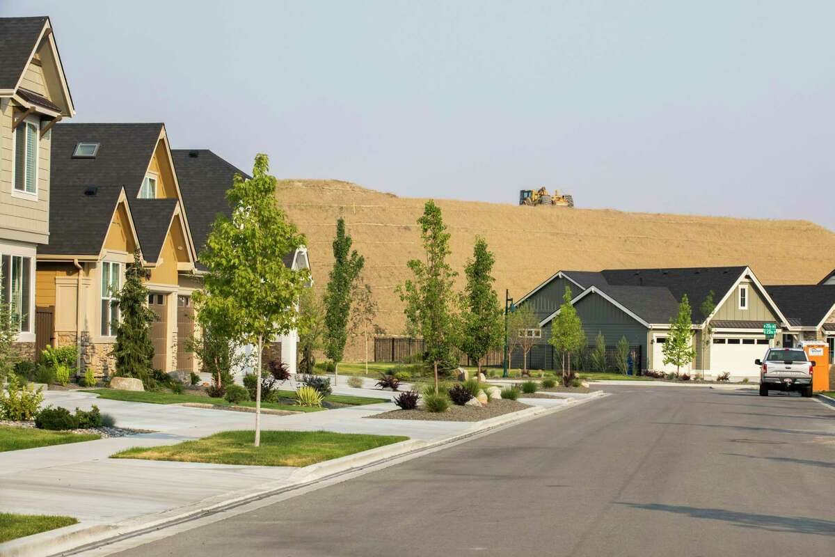 A bulldozer makes way for more houses in Cartwright Ranch, located in the Hidden Springs, Idaho, community north of Boise on July 15.