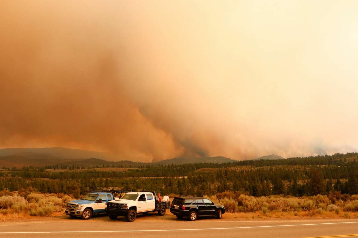 People watch as the Tamarack fire burns unchecked due to drought conditions and gusty winds. The Tamarack fire continues to burn through more than 21,000 acres and is currently 0% contained.