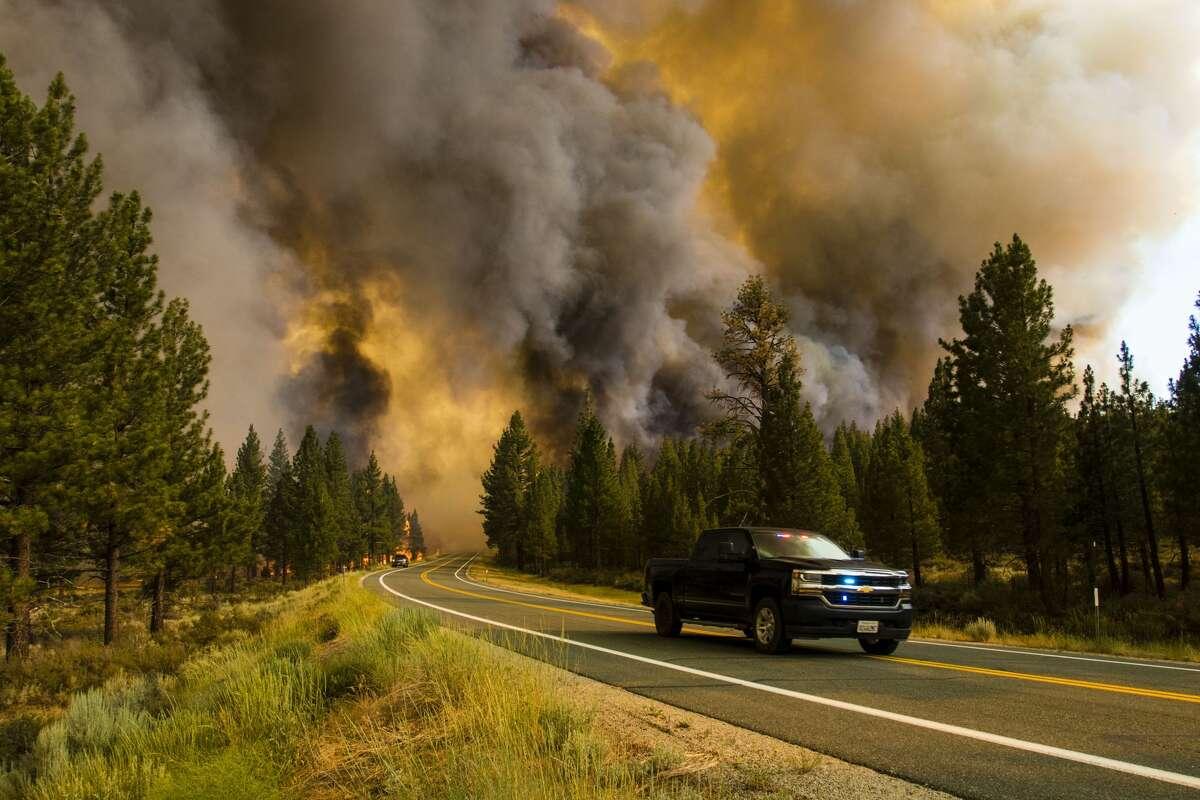 The Tamarack Fire near Markleeville south of Lake Tahoe burns along a roadway.
