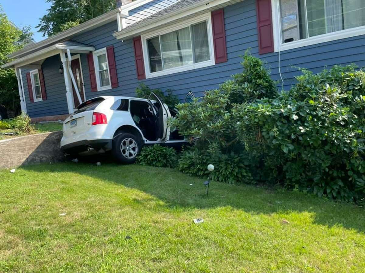 A vehicle crashed into a home on Platt Street in Ansonia, Conn., on Thursday, July 15, 2021, after colliding with another vehicle.