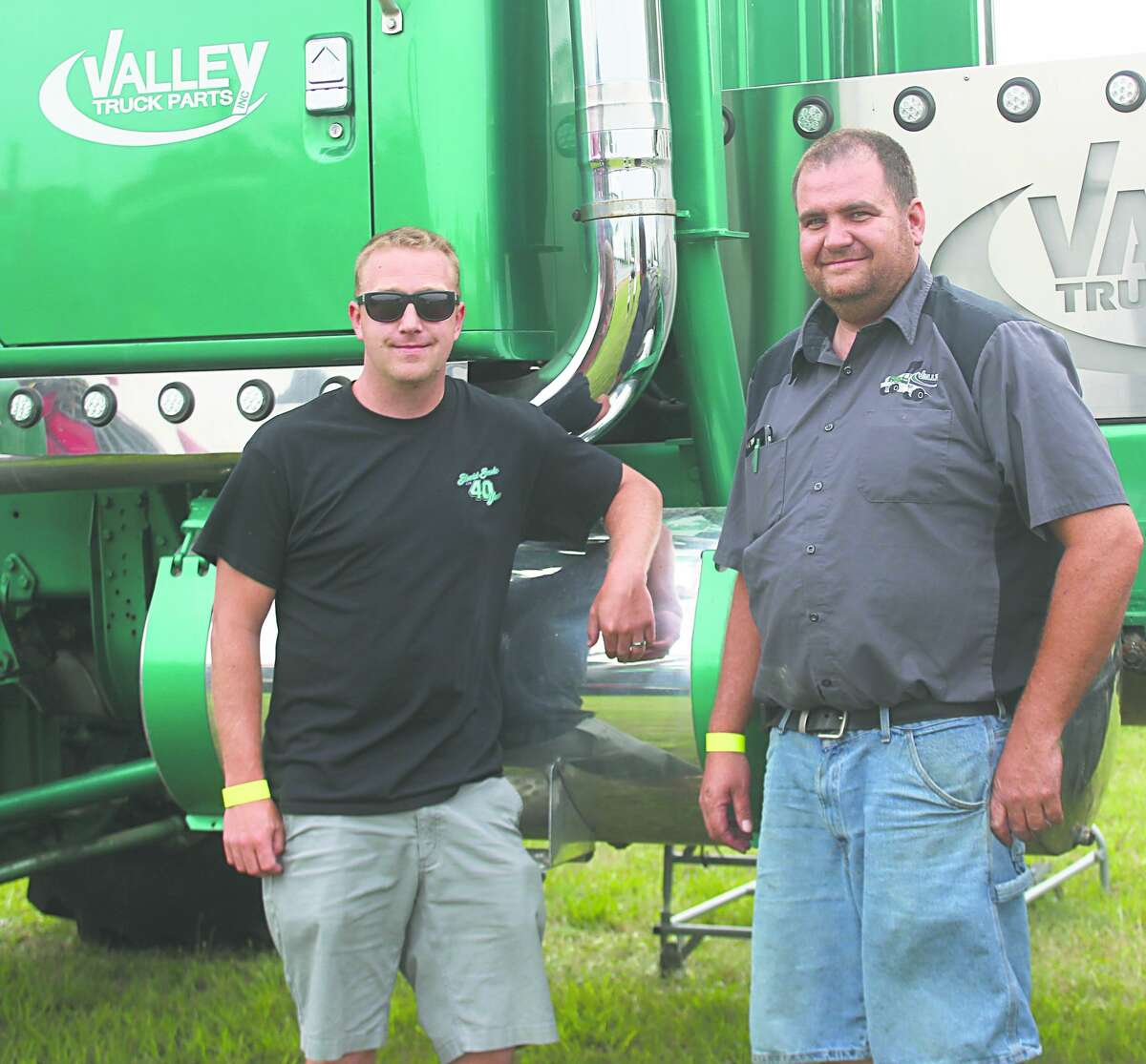 At left, Alex Goodale (left) and driver Bob Venhuizen stand in front of their tractor prior to Friday night's grandstand event at the 2021 Mecosta County Fair.