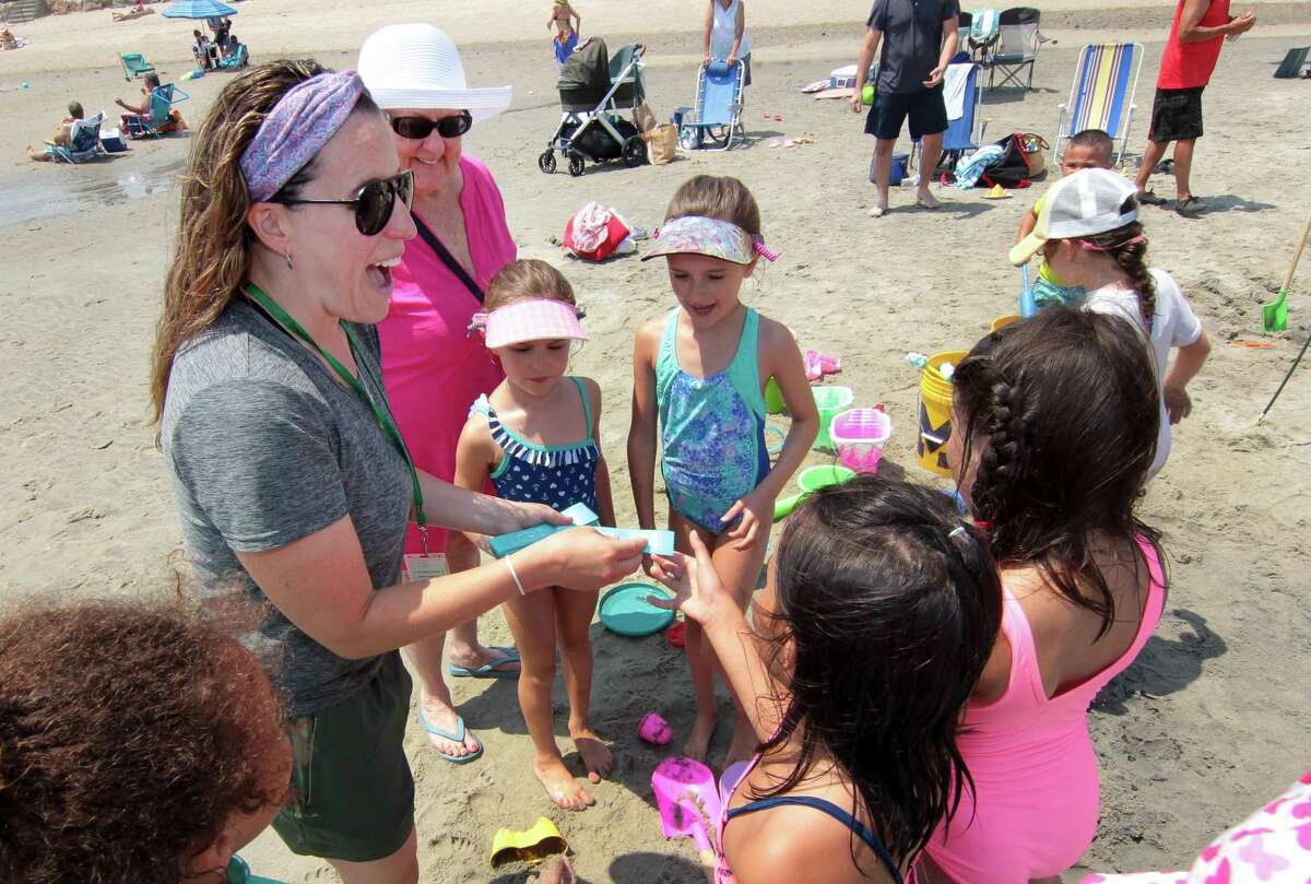 Patricia Troiano, with Greenwich Parks and Recreation, hands out participation ribbons to the kids during the Sand Blast sand sculpture competition at Greenwich Point Park in Greenwich, Conn., on Saturday July 17, 2021. The competition is held in partnership with the Town of Greenwich, and the Greenwich Arts Council.