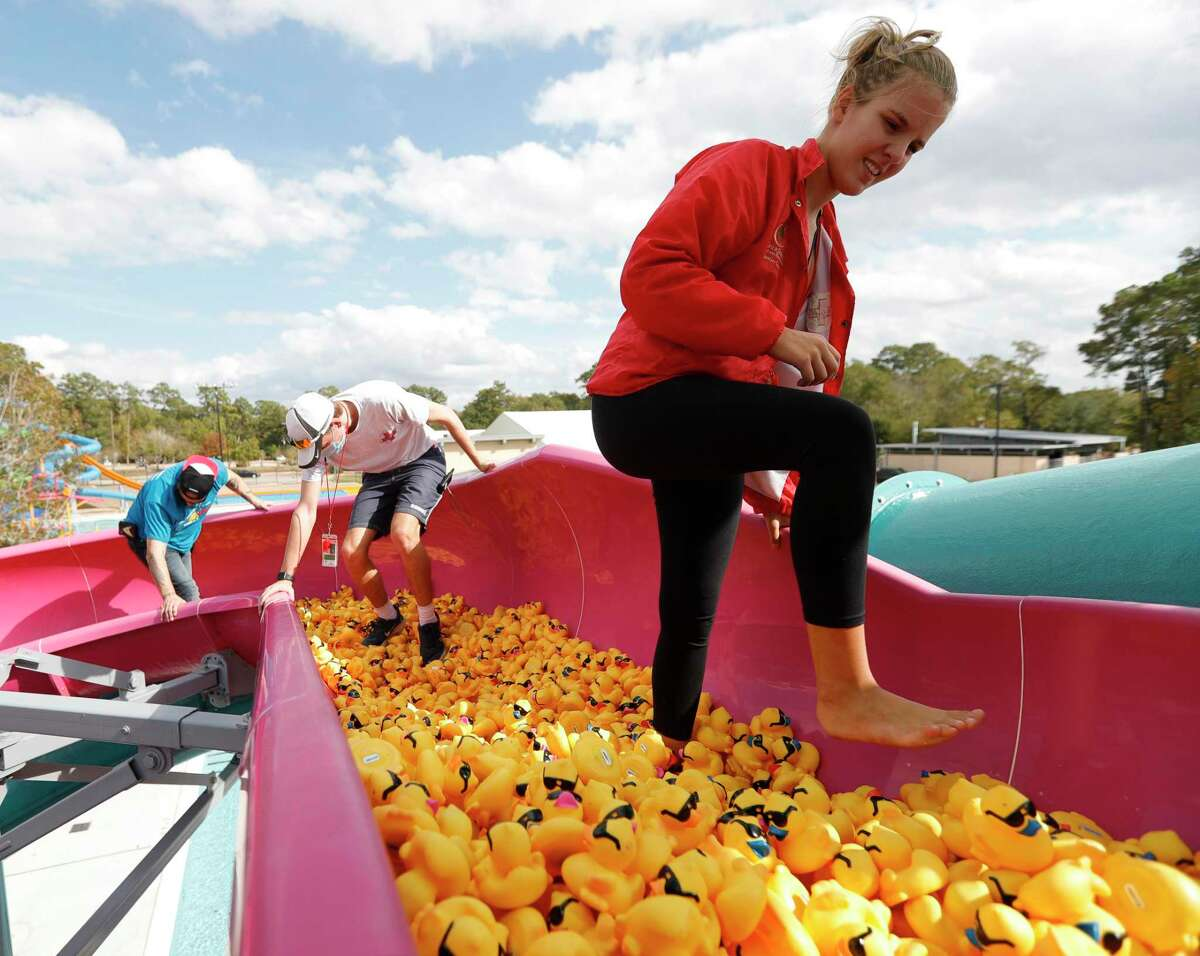 Sam Murfin, right, Krue Flippo and Brian Cook help move 5,000 rubber ducks down a portion of a waterslide before Community Assistance Center's annual duck race at the Conroe Aquatic Center Waterpark, Saturday, Nov. 14, 2020, in Conroe. The event raises money for the non-profit that provides resources and needs to struggling individuals and families in Montgomery County.