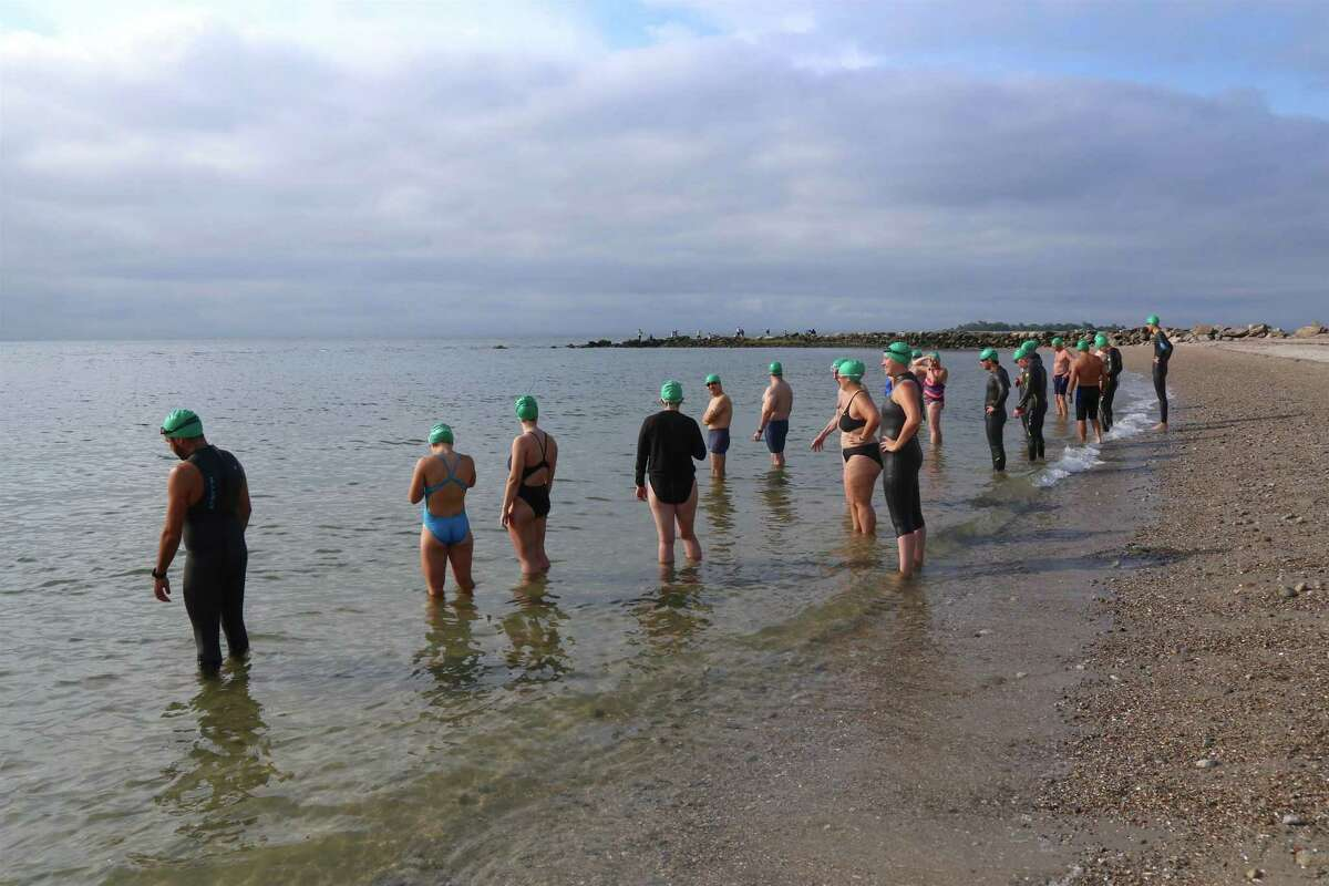 Intermediate swimmers wearing green caps prepare to enter the water at the Point to Point Swim at Compo Beach on Sunday, July 18, 2021, in Westport, Conn.
