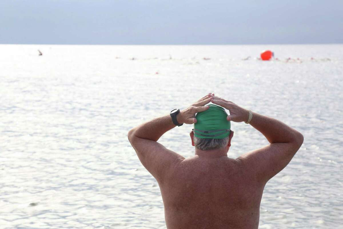 Attila Libertiny of South Salem, N.Y., watches the first group of swimmers round the buoy at the Point to Point Swim at Compo Beach on Sunday, July 18, 2021, in Westport, Conn.