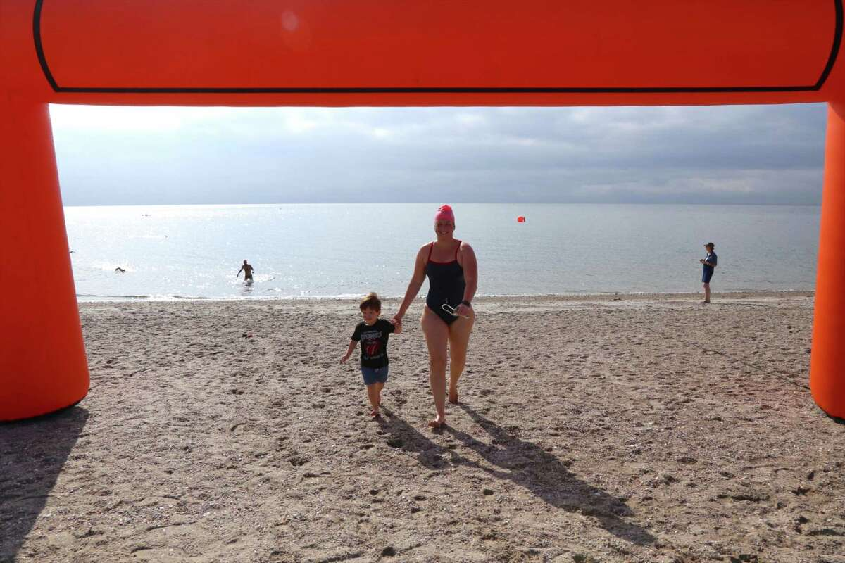 """Ashley Fedor of Weston walks through the finish arch with her son Mateo Llaza, 2, at the Point to Point Swim at Compo Beach on Sunday, July 18, 2021, in Westport, Conn. """"I'm really excited,"""" said Josephine Rojas, the Y's new aquatics director, who was seeing it for the first time. """"The rain seems to be staying off,"""" she said before the start. """"It's a balmy morning, but it's great for swimming."""" Many agreed, but also noted that any open water swim can present some subtle challenges for long distances."""