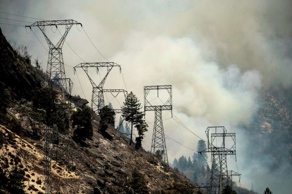 Smoke billows behind power lines as the Dixie Fire burns along Highway 70 in Plumas National Forest on Friday. PG&E said in a preliminary filing with regulators that a falling tree may have sparked the blaze when it hit the lines.