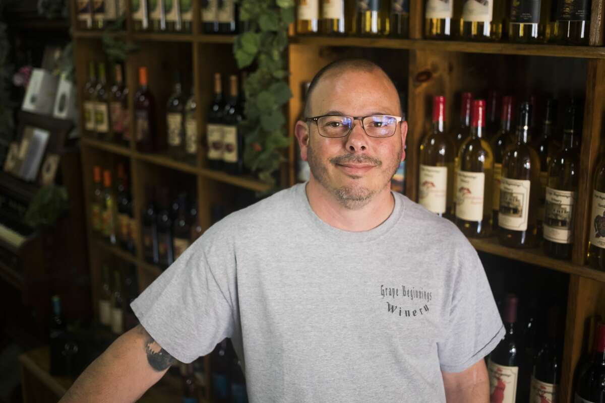 Brent Whitted, co-owner of Grape Beginnings Winery, poses for a portrait Monday, July 19, 2021 at the store in downtown Midland. (Katy Kildee/kkildee@mdn.net)
