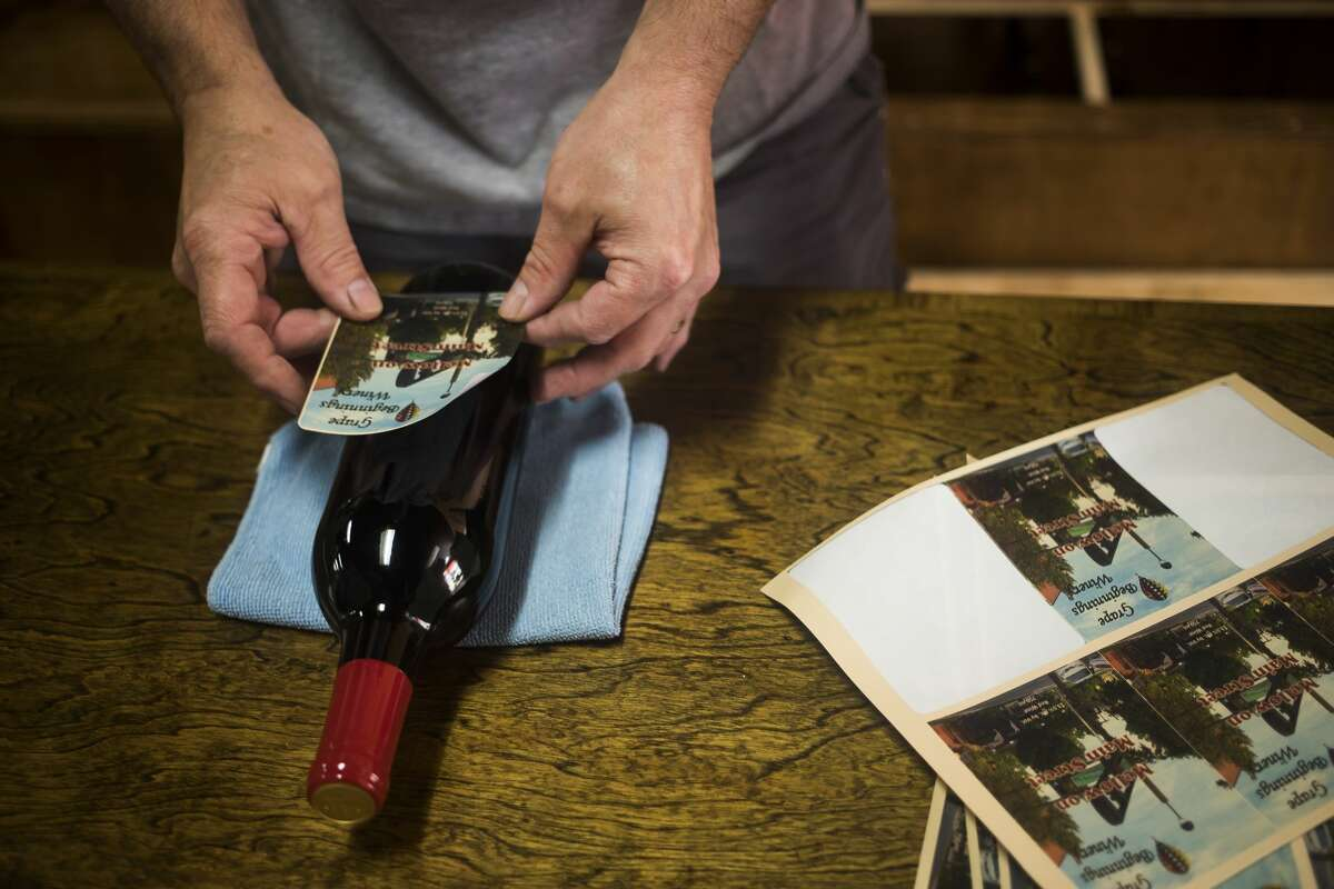 Brent Whitted, co-owner of Grape Beginnings Winery, places a label on a bottle of wine Monday, July 19, 2021 at the store in downtown Midland. (Katy Kildee/kkildee@mdn.net)