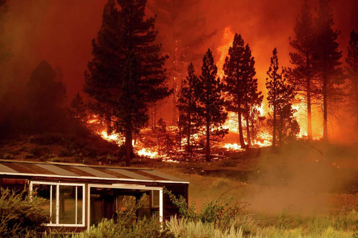 The Tamarack Fire burns behind a greenhouse in the Markleeville community of Alpine County, Calif.