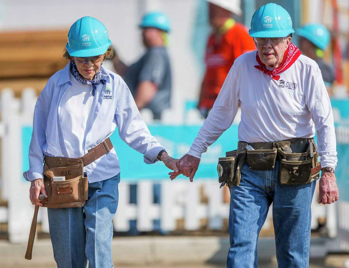 Former President Jimmy Carter holds hands with his wife, former first lady Rosalynn Carter, as they work in August 2018 with other volunteers on site during the first day of the weeklong Jimmy & Rosalynn Carter Work Project, their 35th work project with Habitat for Humanity in Mishawaka, Ind.