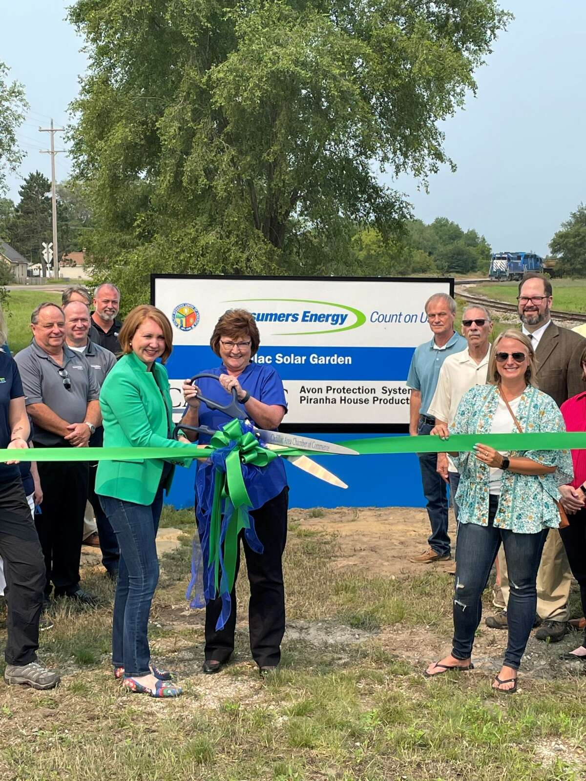 Front, from left, Consumer Energy VP of Costumer Experience Lauren Youngdahl Snyder, joins the mayor of Cadillac, Carla Filkins, to cut the Cadillac Solar Gardens ribbon. Also pictured are other leaders from Consumers Energy, the State of Michigan and the City of Cadillac.