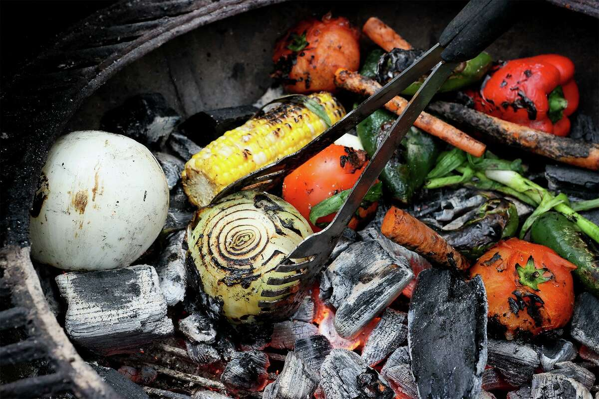 Chuck Blount turns a white onion roasting with corn on the cob, bell peppers, poblano peppers, jalapeño peppers, white onions, carrots, green onions and tomatoes directly on hardwood lump charcoal.