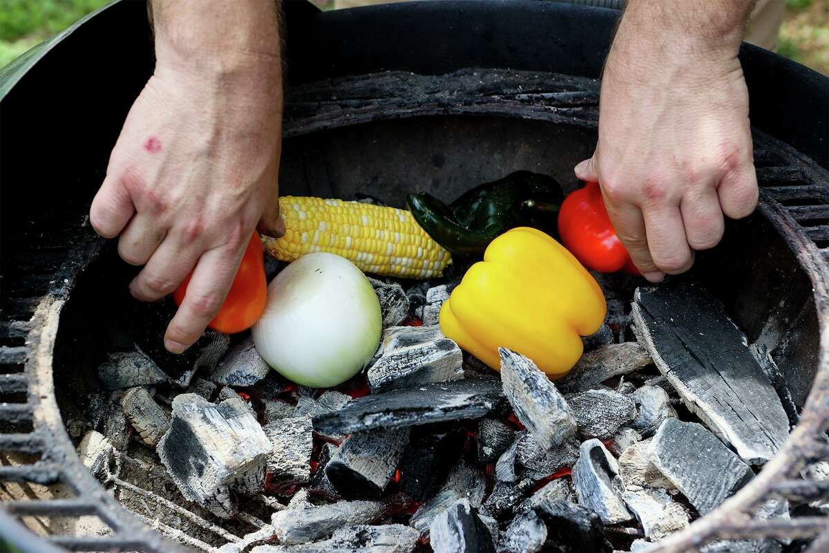 Chuck Blount places vegetables directly on hardwood lump charcoal at the Food Shack, where they will roast for approximately five minutes.