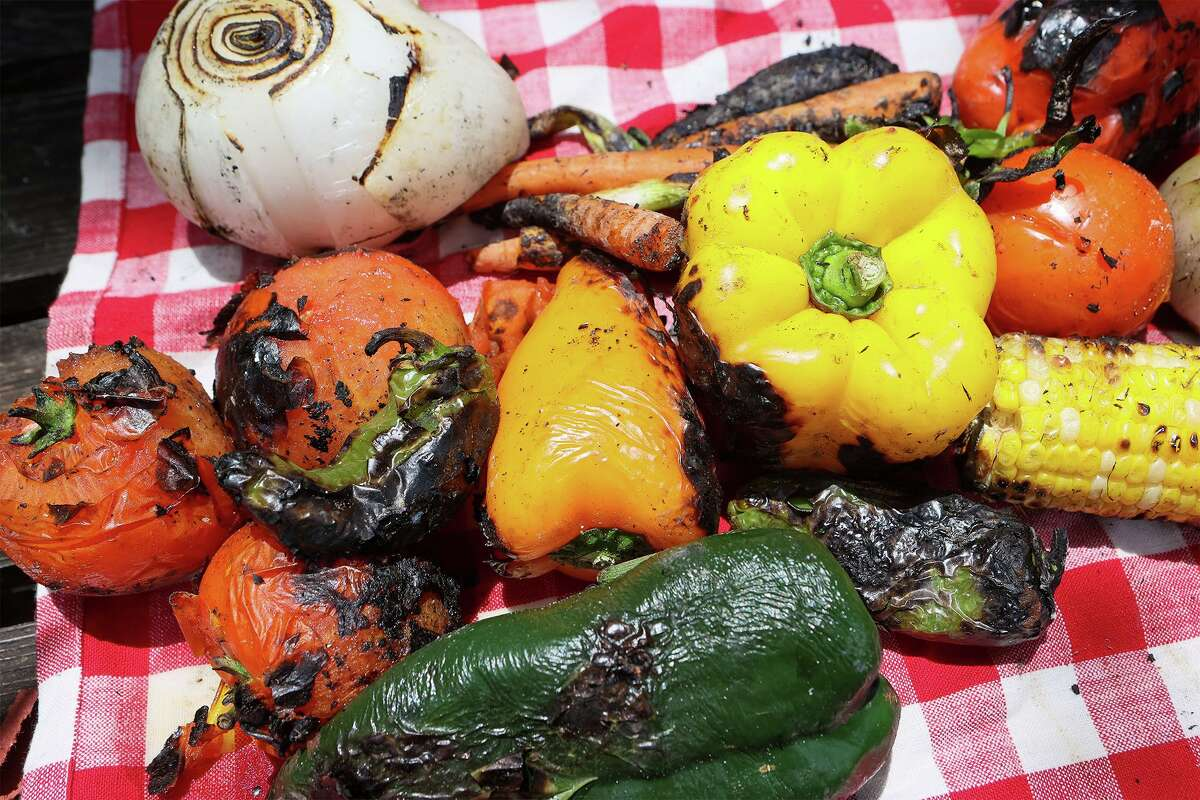 Finished corn on the cob, bell peppers, poblano peppers, jalapeño peppers, white onions, carrots, green onions and tomatoes are seared after being roasted directly on hardwood lump charcoal.