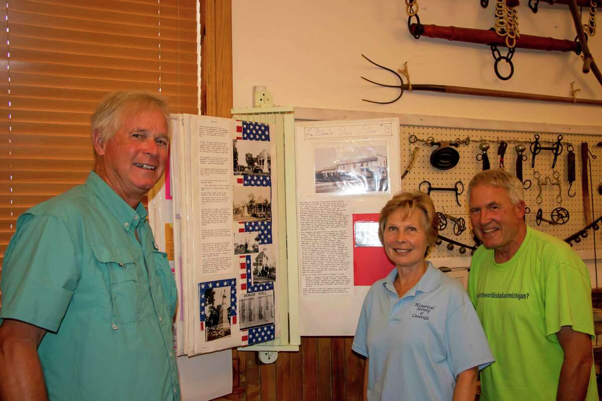 Historical Society of Caseville members Rich Bass, Joyce Miller, and Harold Hoelzle, who were actively involved in putting together the Historic Downtown Caseville Walking Tour, stand beside a flip-through poster board that hangs in the museum. The poster board contains information on the points of interest in the tour. (Bill Diller/For the Tribune)