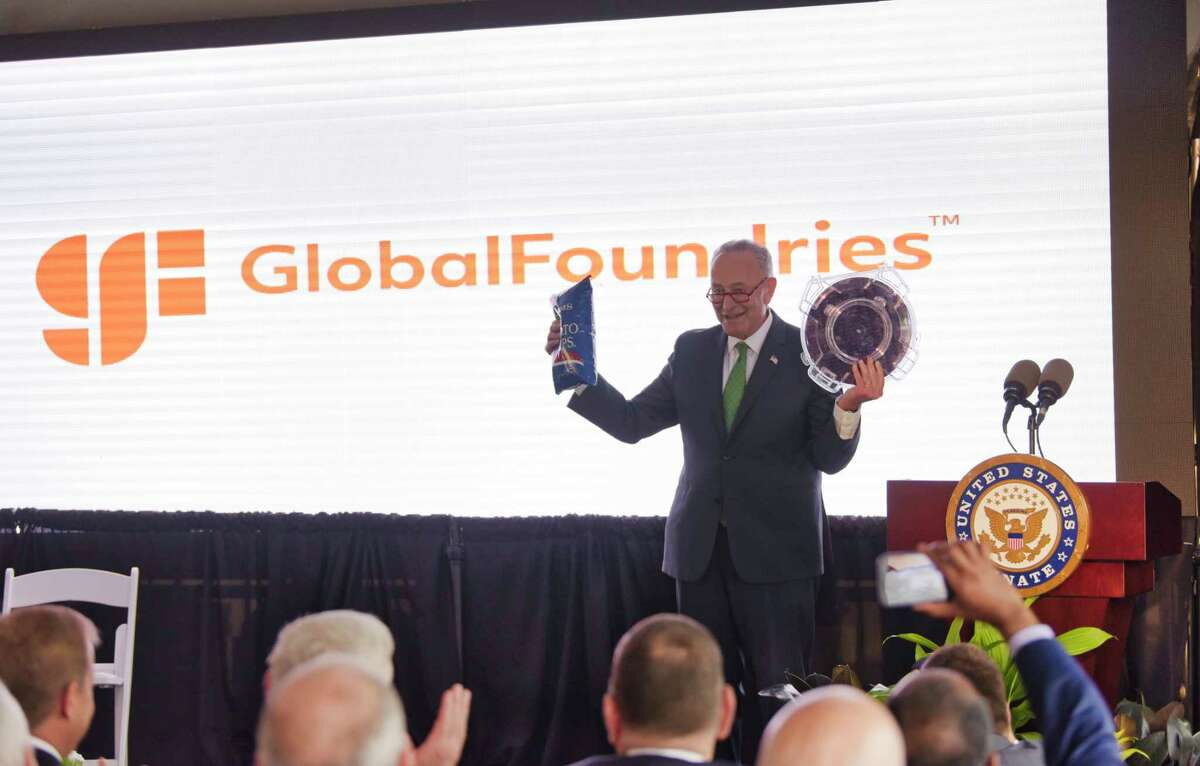 Senate Majority Leader Charles Schumer holds a bag of potato chips and a chip wafer as he jokes that Saratoga County was known for their potato chips and now they will be known for another kind of chip, during an event at GlobalFoundries on Monday, July 19, 2021, in Malta, N.Y. CEO of GlobalFoundries, Tom Caulfield, announced at the Monday event that a second chip plant will be built in Malta. (Paul Buckowski/Times Union)