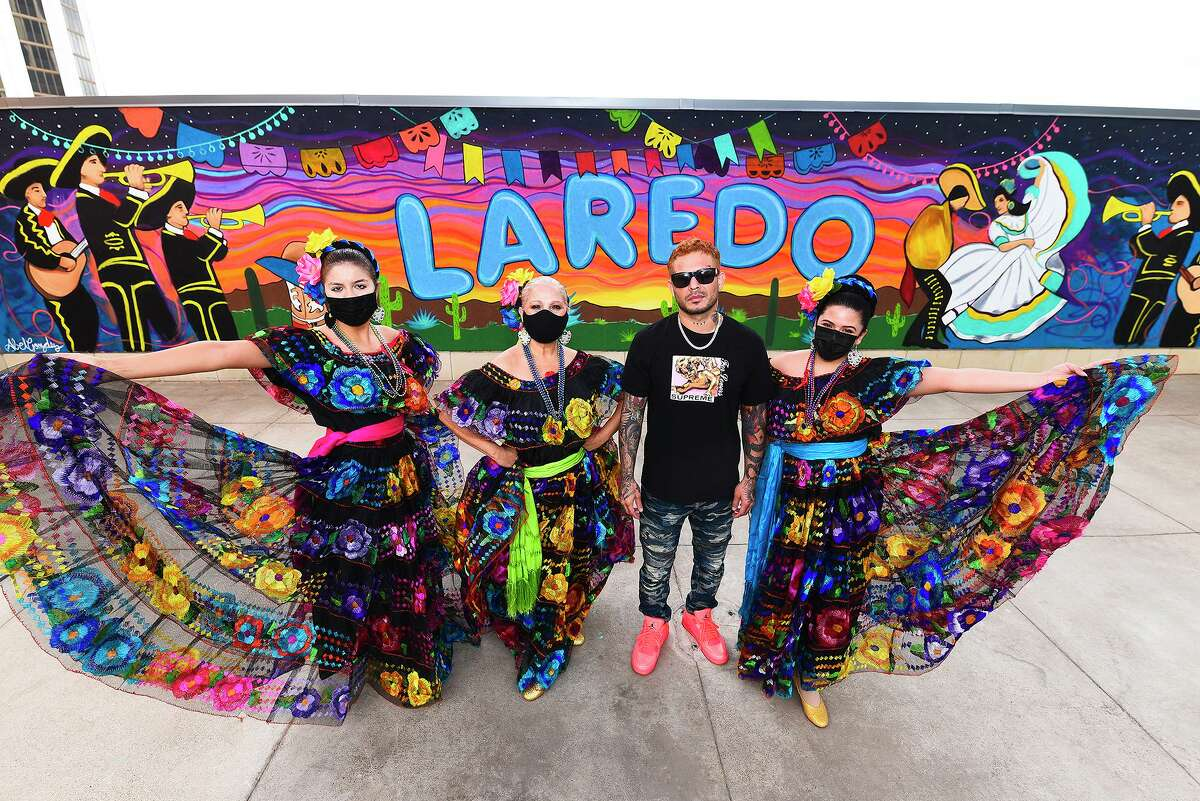Ballet Folklorico Nuevo Santander members Ivanna Benedetto, Sandra Leal and Krista Martinez are joined by muralist Abel Gonzalez on May 15, 2021, during the unveiling of a Laredo mural at the Outlet Shoppes at Laredo.