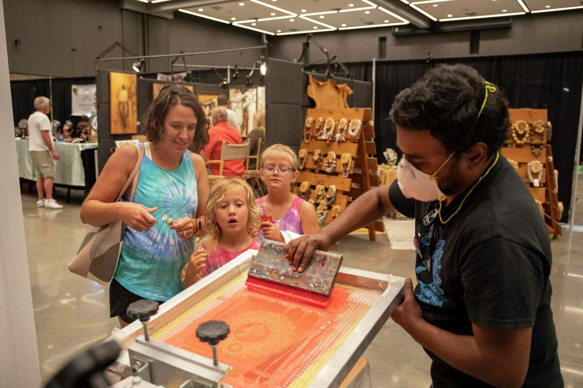 Regan Viney, left, with Leyton Stike, 4, and Ainsley Stike, 7, print a shirt with Mario Kiran during the Celebration of the Arts on Saturday, July 17, 2021 at Bush Convention Center. Jacy Lewis/Reporter-Telegram