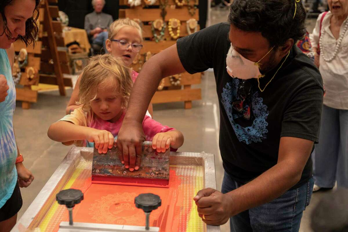 Leyton Stike, 4, prints a shirt with UTPB professor Mario Kiran as Regan Viney, left, and Ainsely Stike, back center, watch during the Celebration of the Arts on Saturday, July 17, 2021 at Bush Convention Center. Jacy Lewis/Reporter-Telegram
