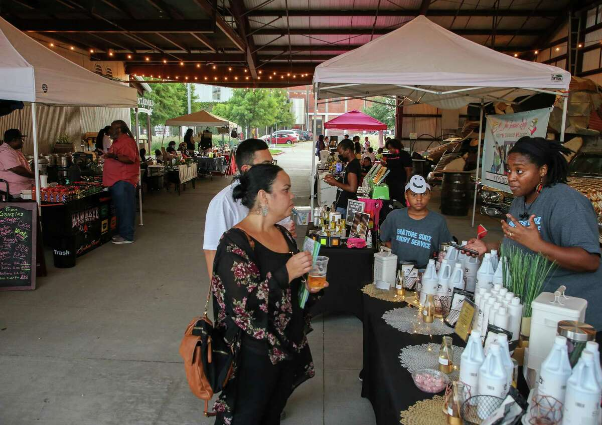 Jessica Tannan, right, talks about her Signature Sudz Laundry company during a Lyons Ave Night Market outside Saint Arnold Brewery on Thursday, July 15, 2021, in Houston. The market happens every Thursday, with more than 20 vendors selling food, crafts and more.