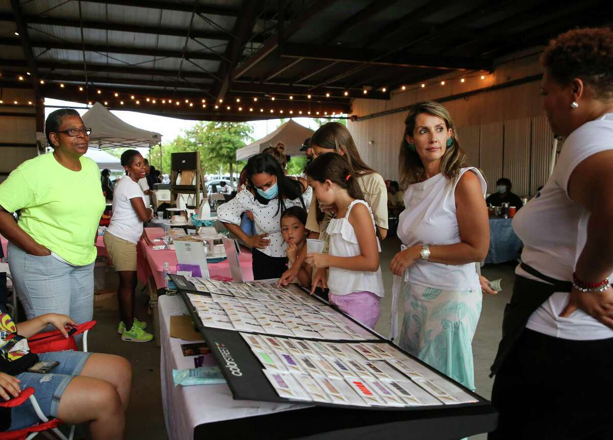 People visit the Lyons Ave Night Market outside Saint Arnold Brewery on Thursday, July 15, 2021, in Houston. The market happens every Thursday, with more than 20 vendors selling food, crafts and more.
