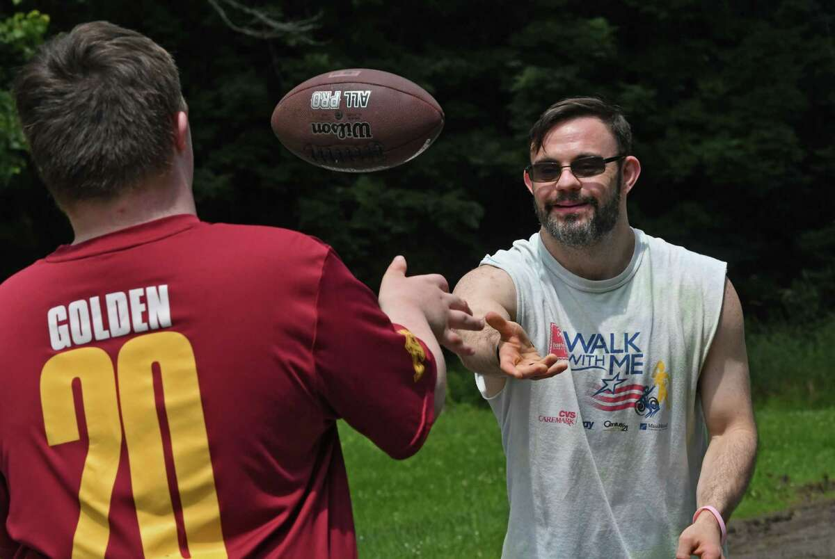 Tom Mooney of Troy, right, throw a football with his friend Alex Hengsterman at Special Olympics camp at the Town of Colonie Mohawk River Park on Monday, July 19, 2021 in Cohoes, N.Y. Mooney learned he was selected to compete in the Special Olympics USA Games next year. (Lori Van Buren/Times Union)