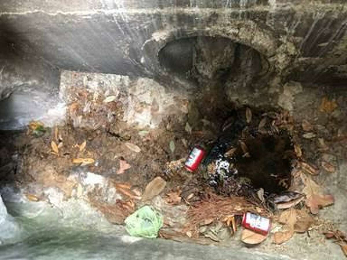 The Woodlands Township and The Woodlands Water Agency have teamed up to tackle problematic pooch poop and other pollutants. In these photographs, township staff display some of illegal waste dumped in township storm drains. According to John Geiger of The Woodlands, 70 percent of the problematic bacteria in water bodies in the township stems from dog fecal matter.