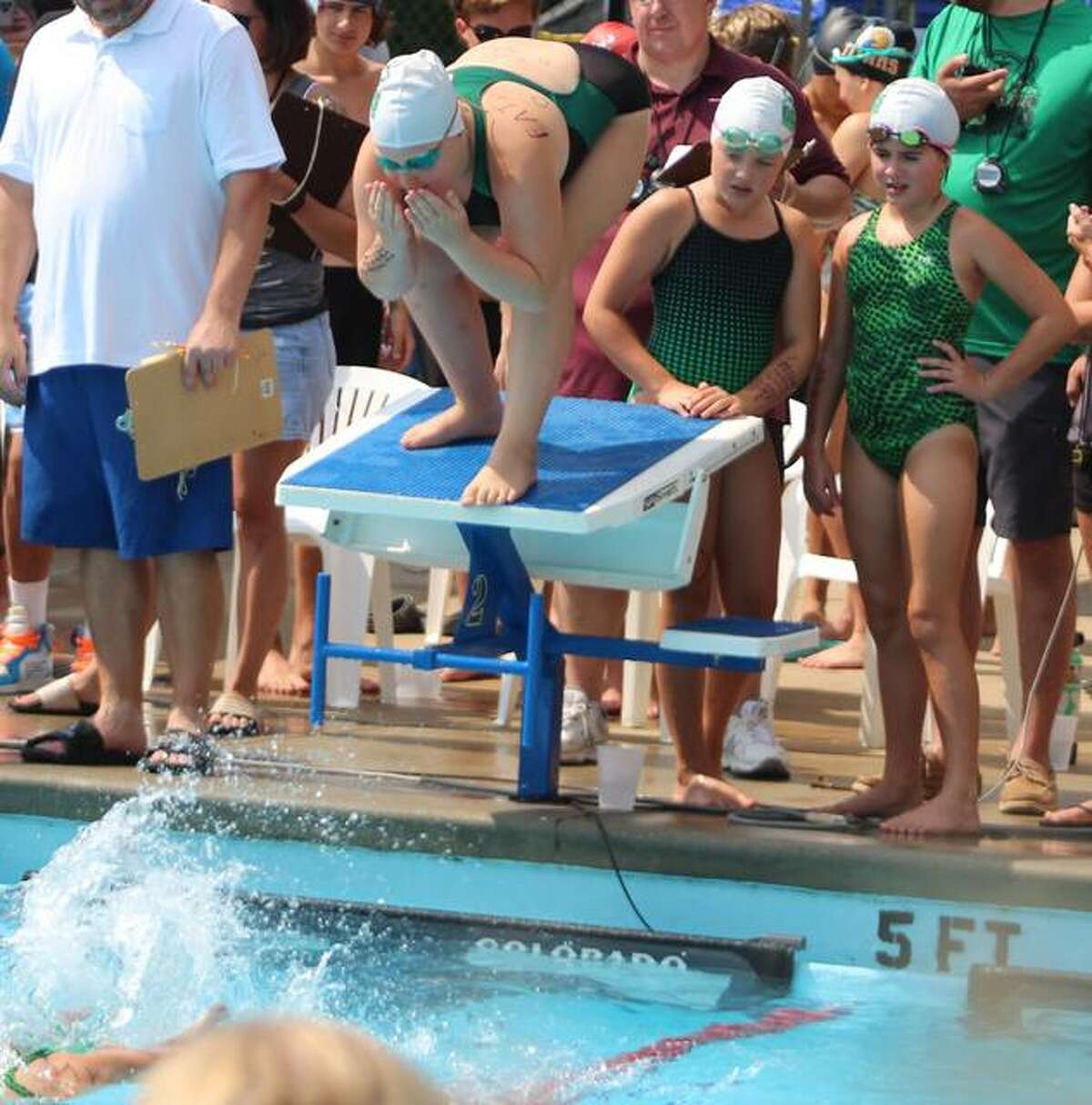 A pair of Collinsville Gators swimmers look for their teammate to touch the wall while another waits on the starting block during a freestyle relay Sunday at the SWISA Championships.