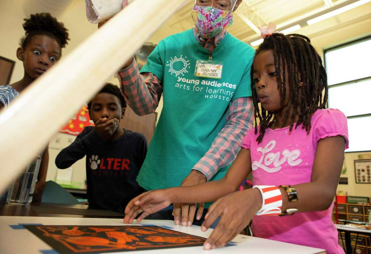 Kennadi Johnson, from left, and Jace Carter react to Xy'Dus Perkins' space screen printing during a creative arts and entrepreneurship camp with artist Danny Russo Thursday, July 1, 2021, at the Buckner Family Hope Center at Reed Road in Houston. Volunteer artists with Young Audiences of Houston were teaching the for South Houston kids art, fashion, business and environmental science at the free week-long camp.