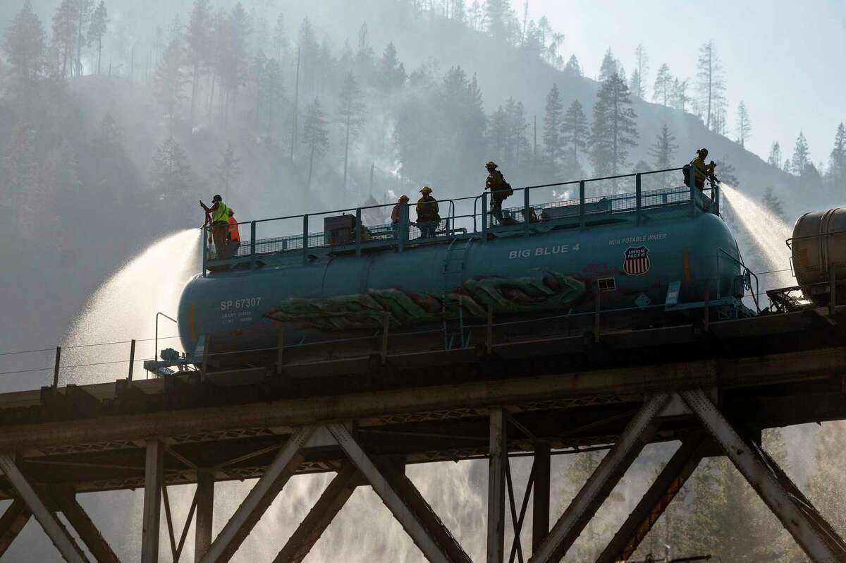 Firefighters spray water from Union Pacific Railroad's fire train while battling the Dixie Fire in Plumas National Forest on Friday.