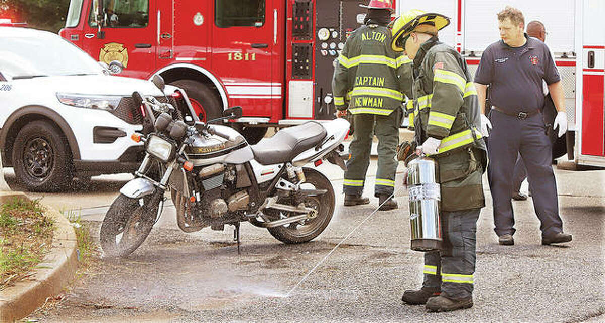 Alton firefighters wash bio-hazard material from Alby Street with an extinguisher following a motorcycle and car collision about noon Monday.