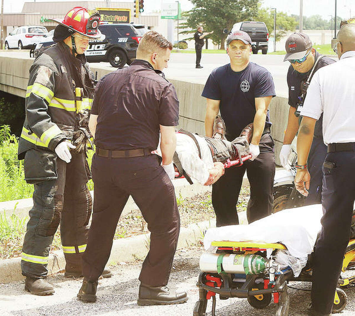The operator of a Kawasaki motorcycle is raised onto a stretcher for transport to a local hospital Monday at the intersection of Alby and Delmar streets in Alton at about noon. The motorcycle collided with the front end of a Toyota Avalon. The Avalon drive did not appear injured in the collision.