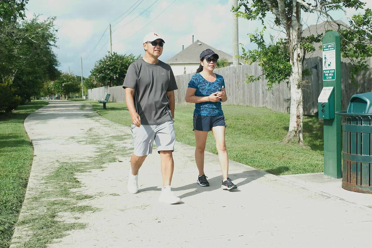 Stephen and Theresa Le enjoy a morning walk along the trail around Lake Friendswood Park. A developer, Westwood, has agreed to install storm-sewer pipe along the south and southeast sides of the park to address a problem with flooding on the trail related to nearby home development in League City.