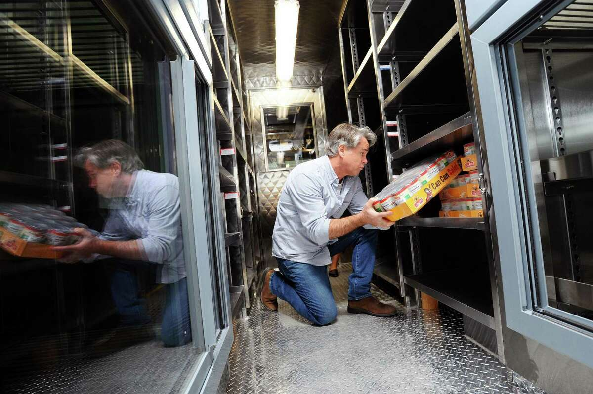 Volunteer Bill Bradley, of Weston, stocks the shelves of the Person-To-Person mobile food pantry in 2018.