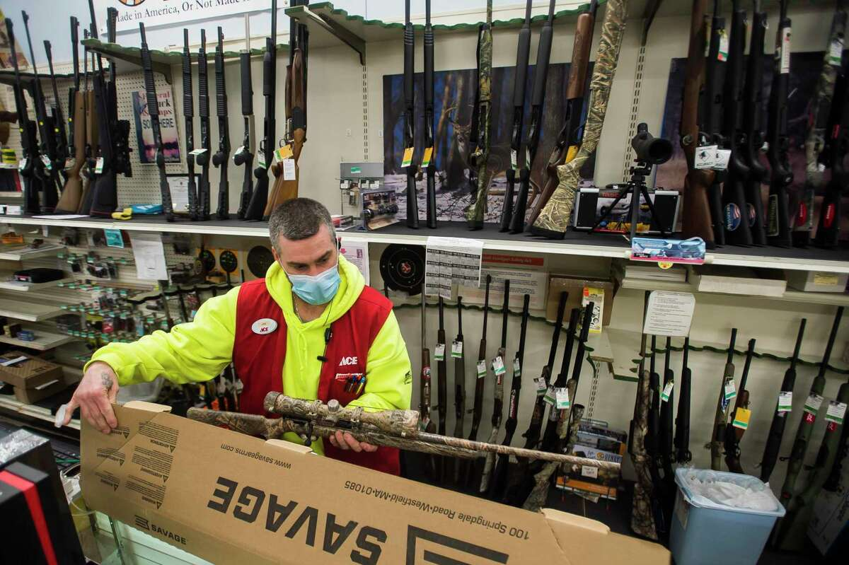 File photo. Midland Ace Hardware manager of sporting goods Jon Leiner assists a customer in purchasing a rifle Thursday, Feb. 11, 2021 at the store in Midland, Mich.