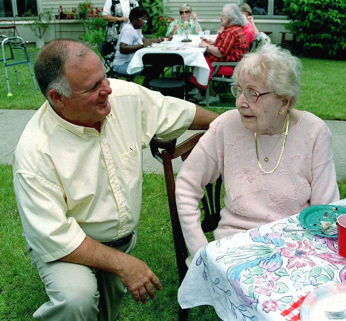 Brooks Temple shares a chat with Chestnut Grove resident Annanda Devlin in an image from 2011.
