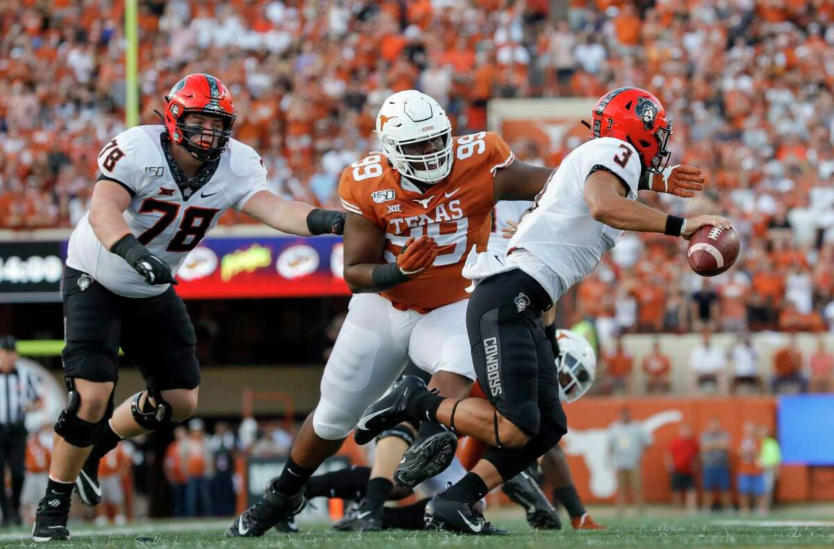 Keondre Coburn #99 of the Texas Longhorns pressures Spencer Sanders of the Oklahoma State Cowboys in the first quarter at Darrell K Royal-Texas Memorial Stadium on September 21, 2019 in Austin, Texas.
