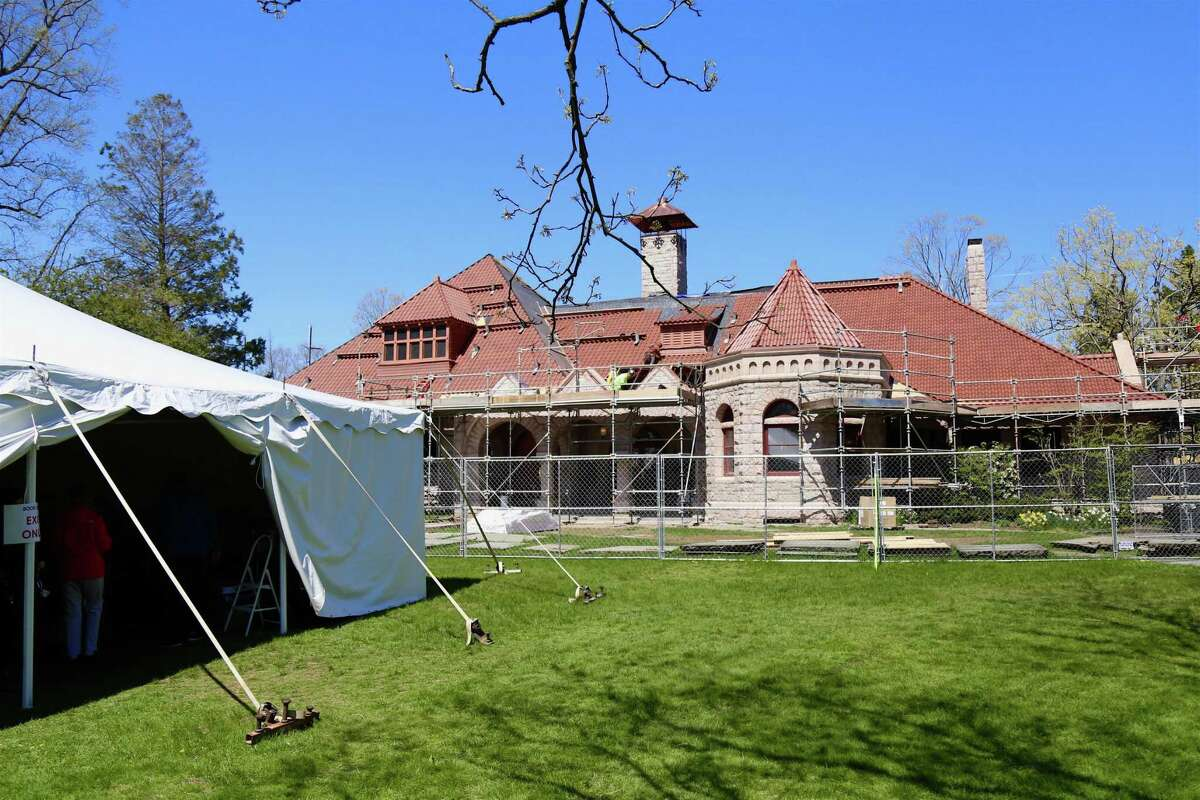 Workers repair the roof to the historic building, while the book sale goes on in the tent outside for the Pequot Library's Sping Fling Book Sale, Friday, April 23, 2021, in Fairfield, Conn.