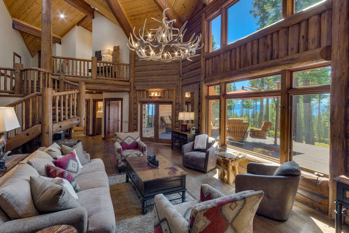 The luxury log cabin design features huge windows overlooking the landscape.