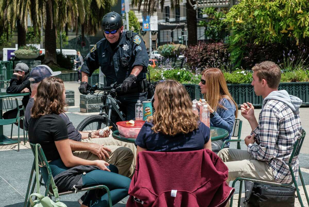 Sgt. Rich Jones chats with the Davainis family, who are visiting from Redding, while on patrol in Union Square. Nearly 30 uniformed officers, on bicycle and foot, have been deployed to tourist areas.