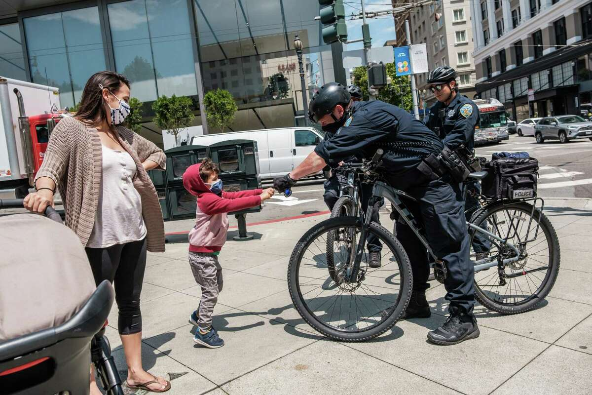 Sgt. Rich Jones greets Ben Parnass, 4, and his mother Sara, who are visiting from Los Angeles, while on patrol in Union Square.