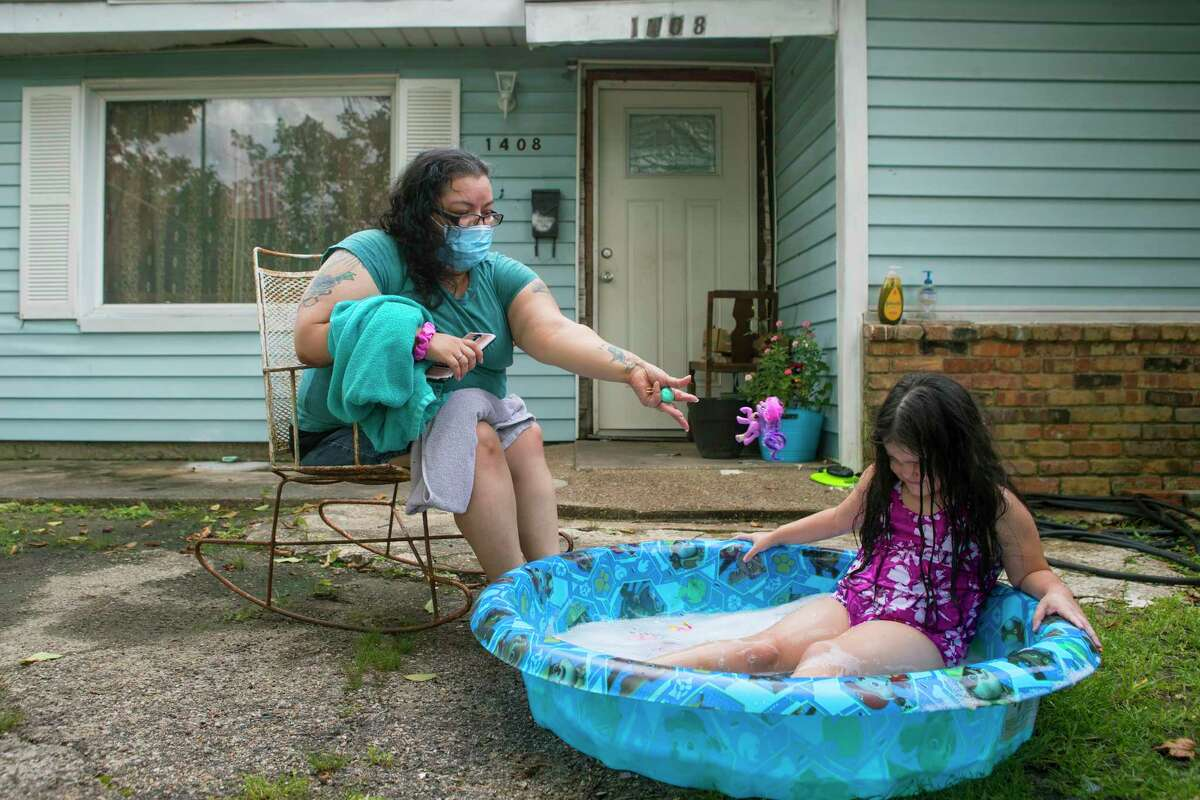 Diana Gonzalez sits outside her house watching her daughter, Maddilyn, play in her baby pool Monday in Galena Park
